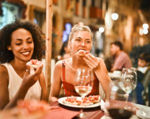 Two women eat Italian food and drink wine at a busy restaurant.